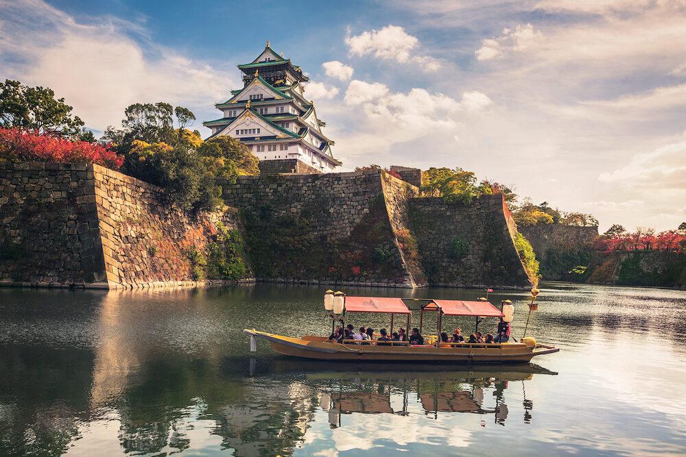 OSAKA, JAPAN - Touristic boat with tourists along the moat of Osaka Castle is one of the best activities you can experience around Osaka Castle area, Osaka, Japan.