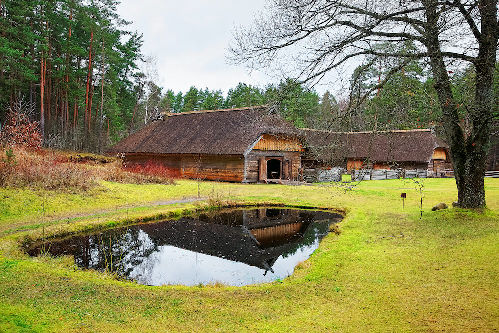 Riga Latvia - Old house with artificial pond in Ethnographic open air village of Riga Latvia Baltic country