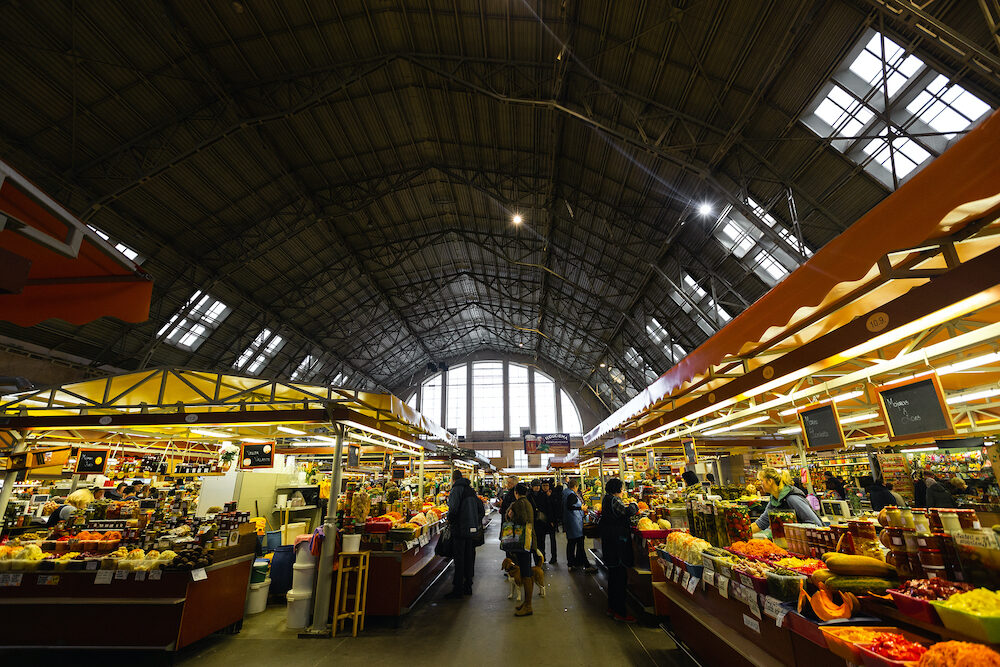 RIGA, LATVIA - Riga Central market grocery pavilion, people buying food - Former zeppelin hangars - Rigas Centraltirgus