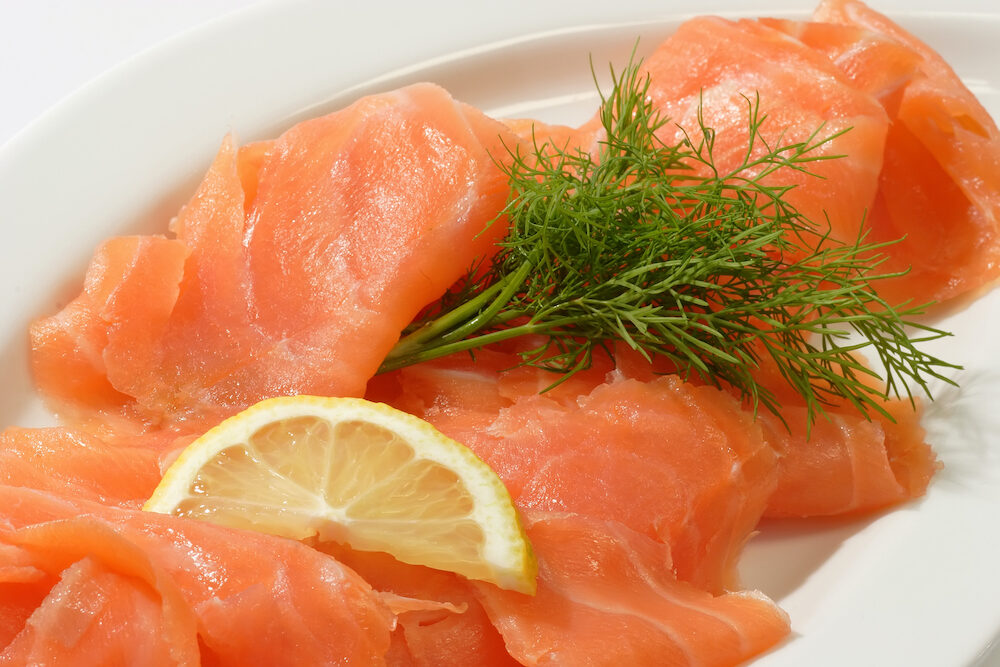 Smoked salmon with slice of lemon and herb on a plate