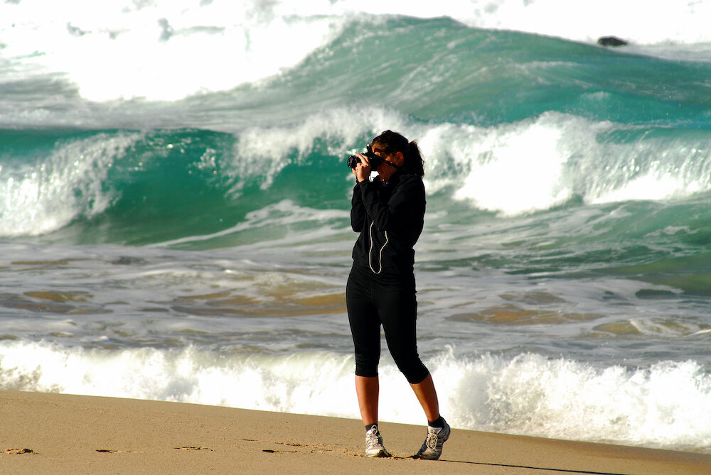 Photographer snapping away with surf in background.
