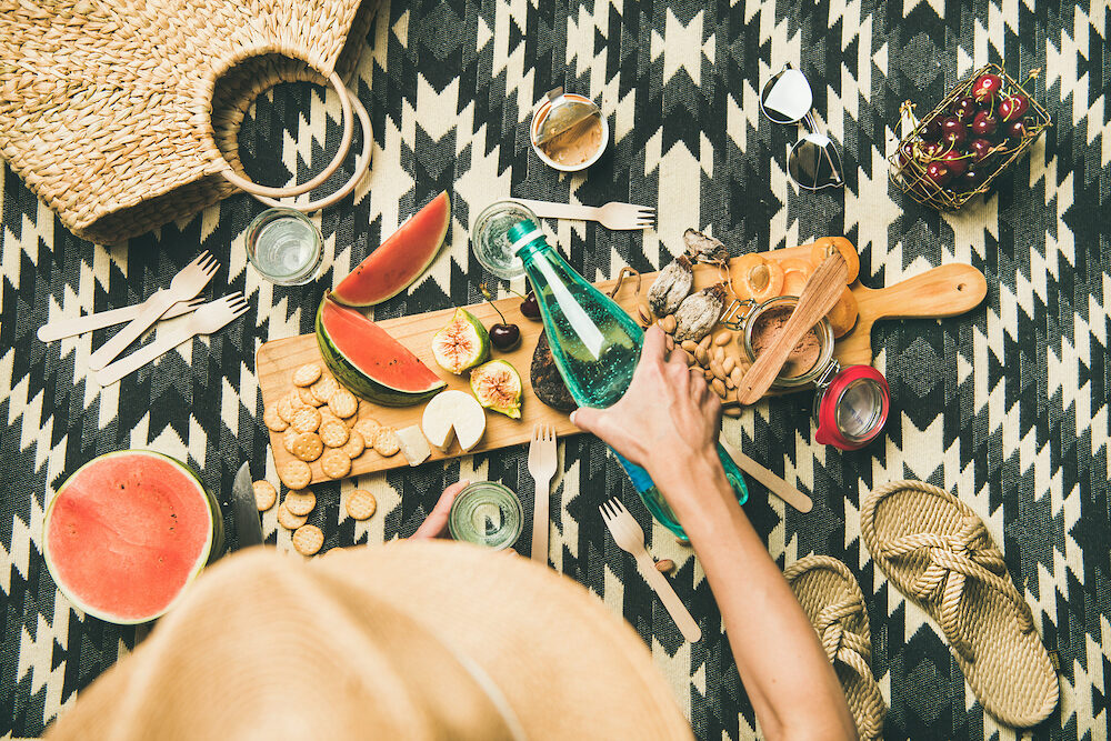Summer beach picnic setting. Flat-lay of charcuterie board with snacks, watermelon, cherries, beach feminine accesories over picnic blanket, top view, copy space. Girl pouring soda from bottle