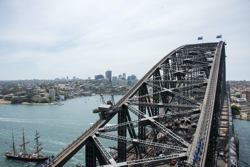 SYDNEY,NSW,AUSTRALIA-Sydney Harbour Bridge, three-masted tall ship and tourists climbing steel arch overlooking cityscape in Sydney, Australia.