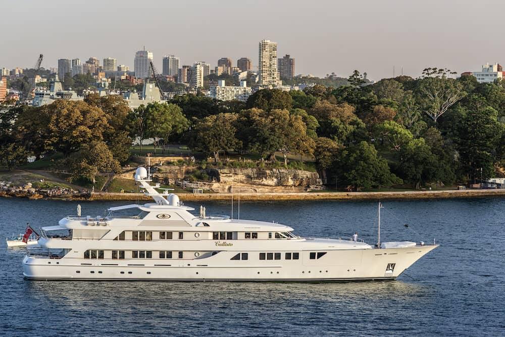 Sydney, Australia - : The white luxurious Callisto yacht in the bay under an evening twilight sky.