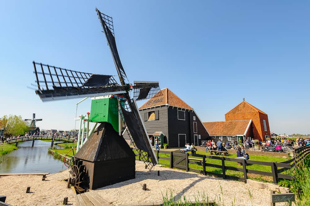 Zaanse Schans, Netherlands - Tourists sightseeng traditional Dutch rural houses and windmills in Zaanse Schans, is a typical small village within Amsterdam area.