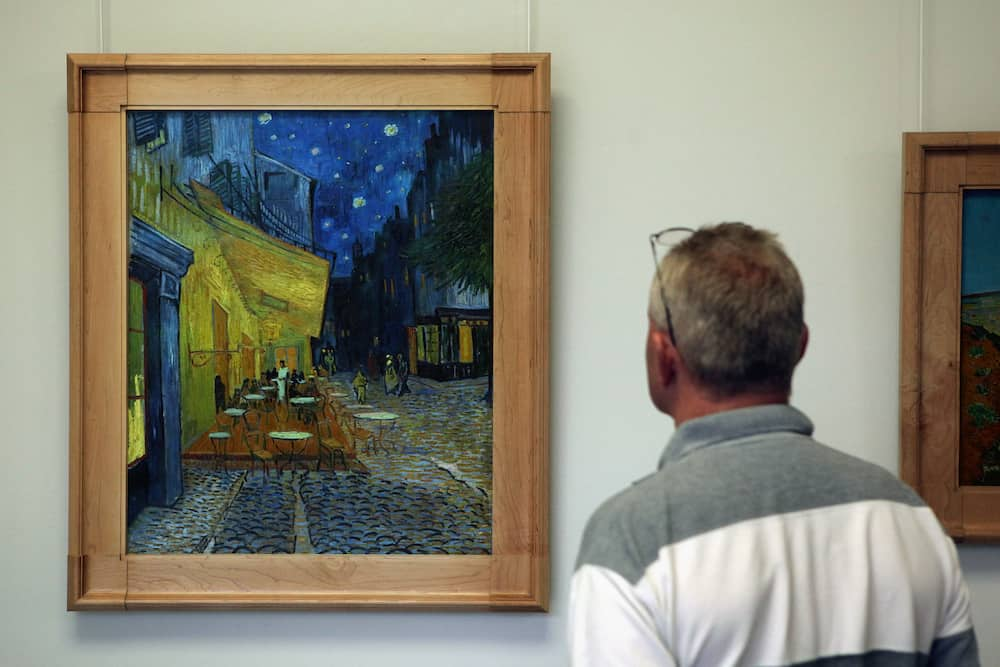 OTTERLO, NETHERLANDS - Visitor looks at the painting Cafe Terrace at Night (1888) by Vincent van Gogh in the Kroller Muller Museum in Otterlo, Netherlands.