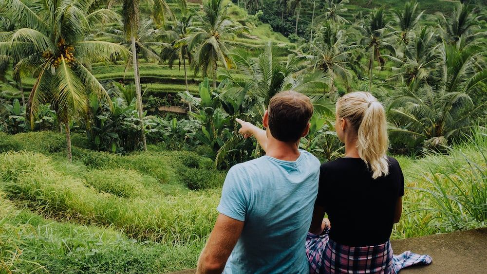 Happy couple explore Tegalalang rice terraces near Ubud, Bali, Indonesia. Summer travel vocation concept
