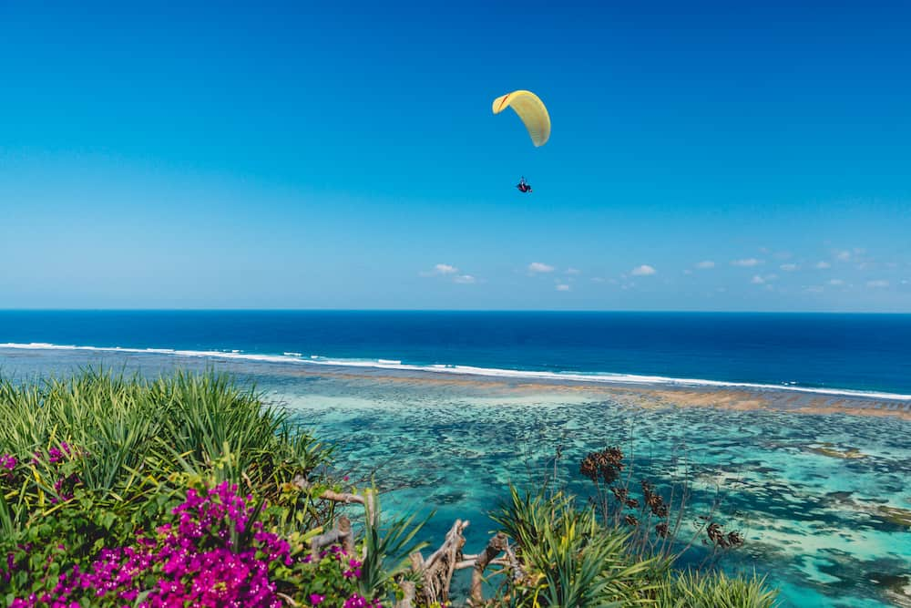 Shore and blue ocean with paraglider in tropical island.