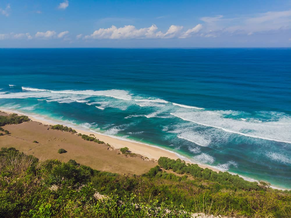 Top aerial view of beauty Bali beach. Empty paradise beach, blue sea waves in Bali island, Indonesia. Suluban and Nyang Nyang place