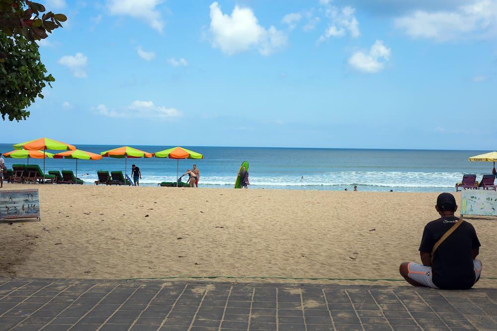 Seminyak, Bali. Wide sand beach with tourists, near Kuta Indonesia Bali