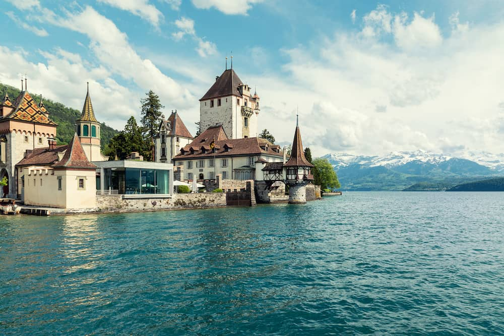 Beautiful little tower of Oberhofen castle in the Thun lake with mountains on background in Switzerland, near Bern