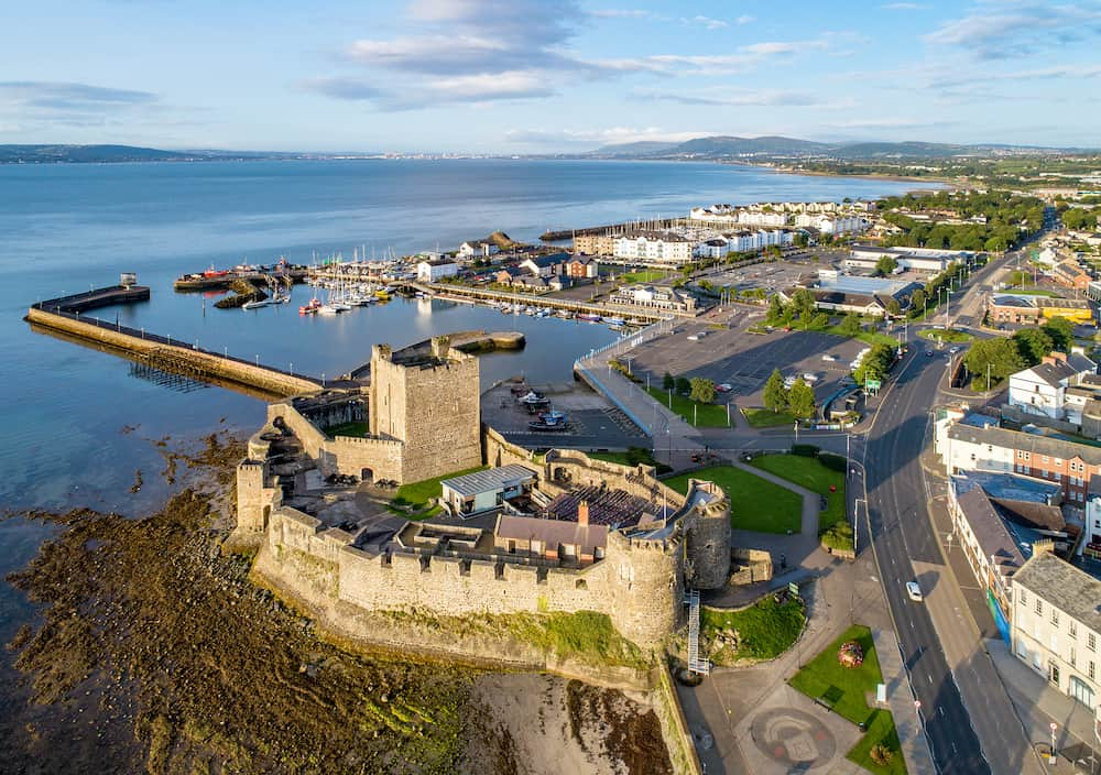 Belfast Lough. Medieval Norman Castle in Carrickfergus in sunrise light. Aerial view with marina, yachts, parking, breakwater, sediments and far view of Belfast in the background