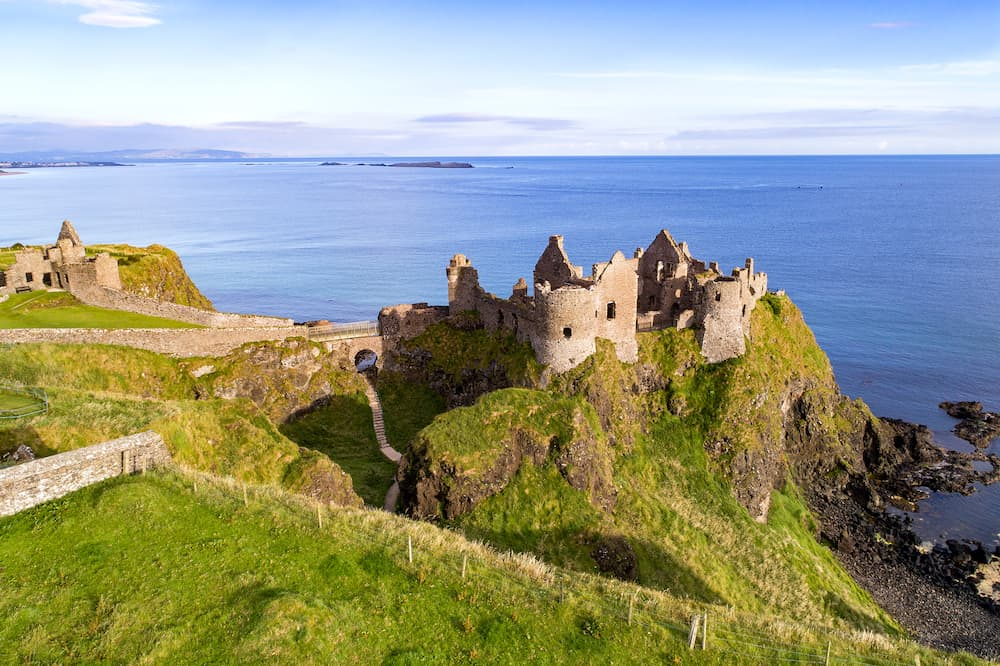 Ruins of medieval Dunluce Castle on a steep cliff. Northern coast of County Antrim Northern Ireland UK. Aerial view.