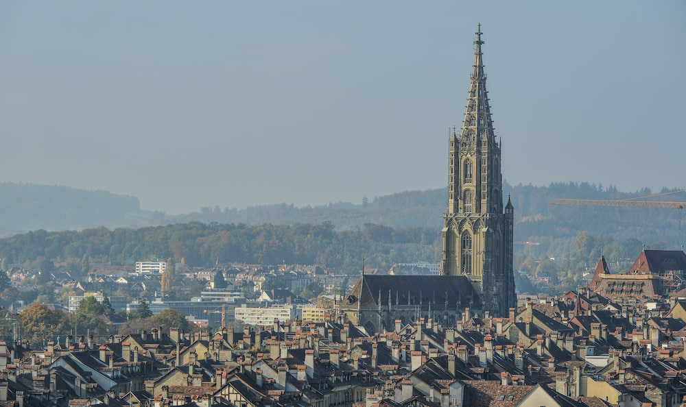 Bern, Switzerland - Ancient church with cityscape of Bern, Switzerland. Bern is built around a crook in the Aare River.