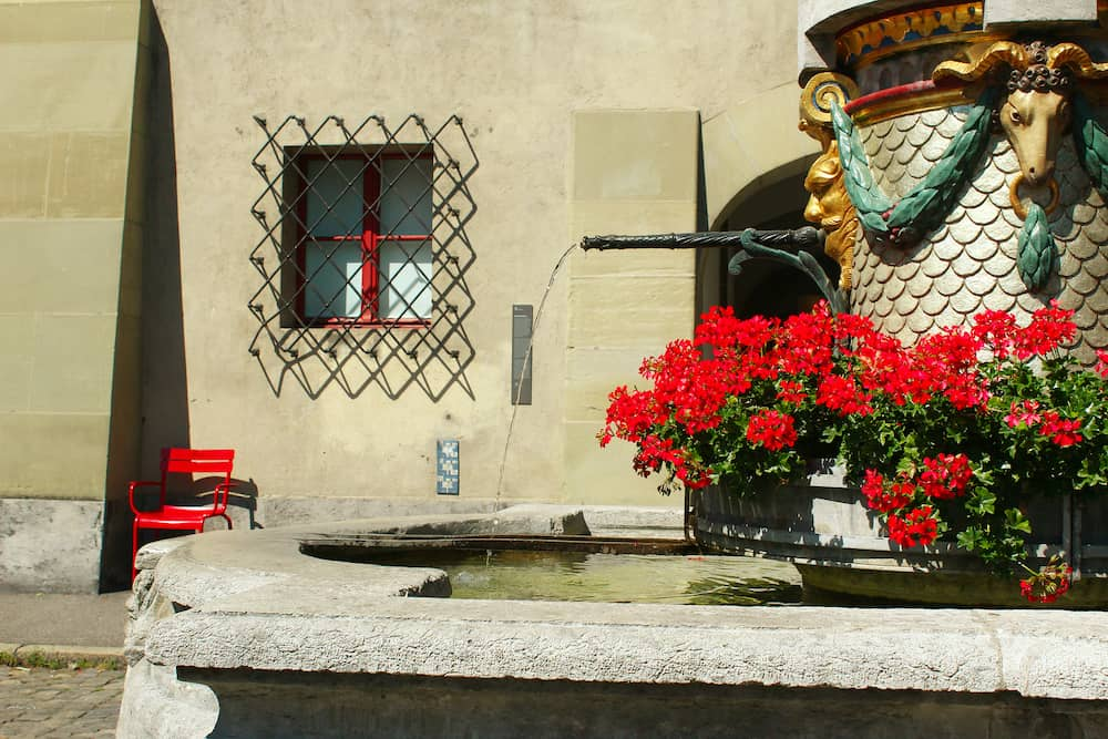 Fountain with water and red flowers at the ancient square Münsterplatz near the cathedral in Bern, Switzerland, during summer