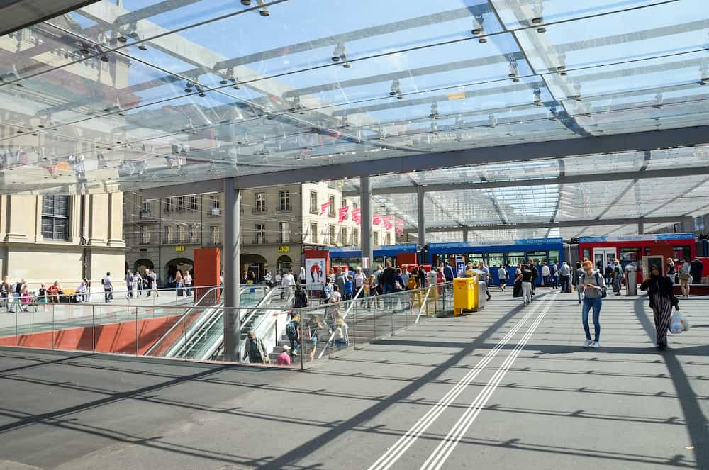 Bern, Switzerland - People walking under the roof by tram station. The station is adjacent to the main train station. Tram in background. Public transport. Daily life. Swiss capital