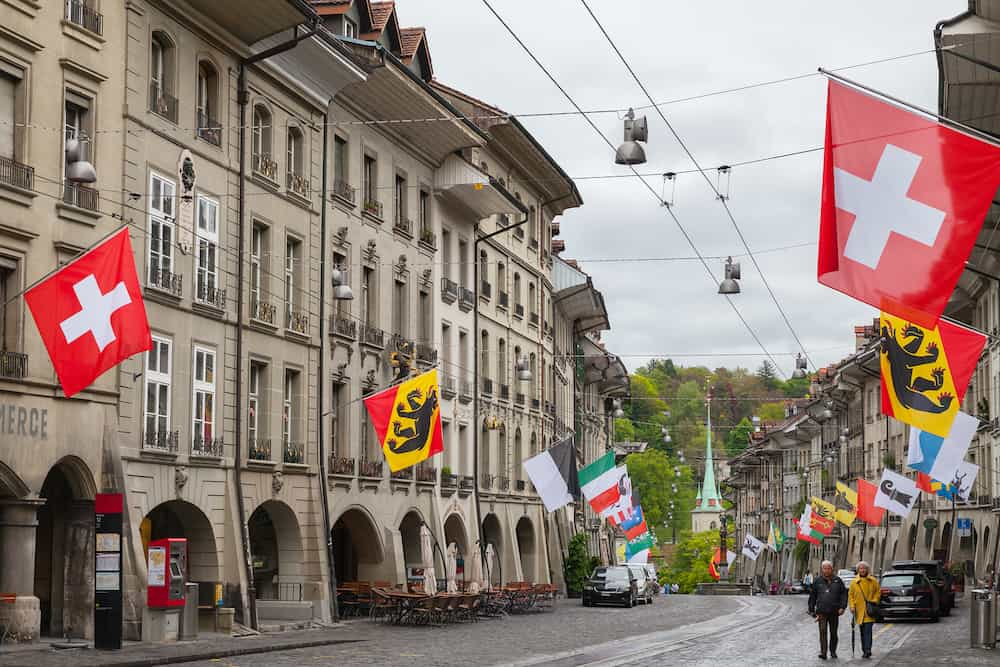 Bern, Switzerland - Street view of Kramgasse. It is one of the principal streets in the Old City of Bern. People walk under colorful flags of Swiss cantons