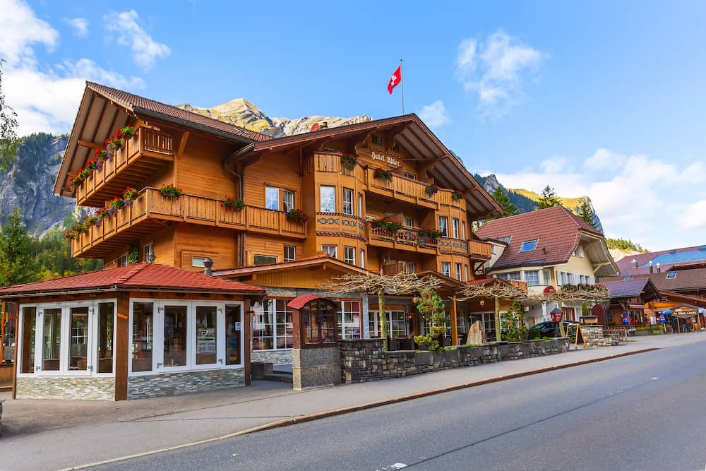 Kandersteg, Switzerland Street view with colorful wooden house, Swiss flag and mountains panorama, Canton Bern, Europe