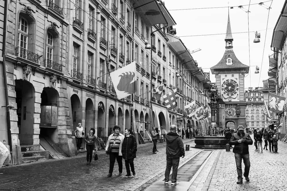 Bern, Switzerland - Street view of Kramgasse. It is one of the principal streets in the Old City of Bern. People walk under flags of Swiss cantons. Retro stylized black and white photo