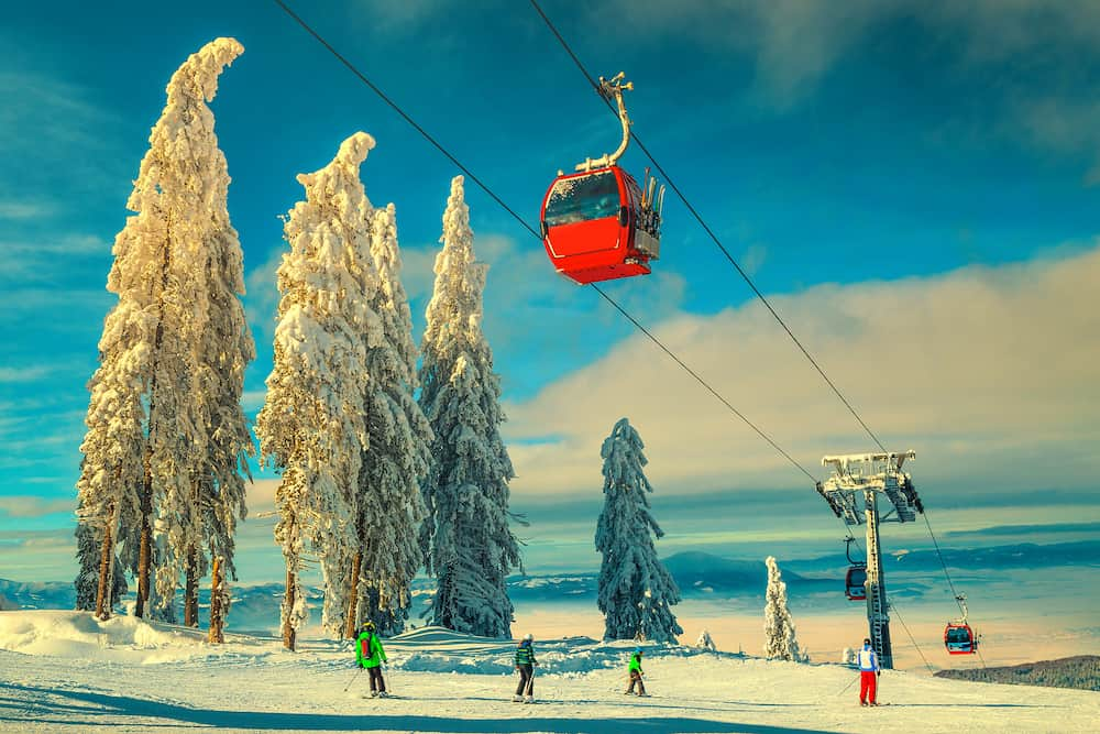 Picturesque snow covered trees and winter ski resort with colorful fast cable cars. Skiers on the ski slope in Poiana Brasov famous ski resort, Transylvania, Romania, Europe