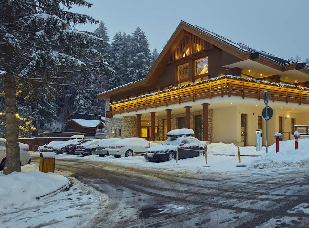 Poiana Brasov, Romania - Snowy luxurious guesthouse with Christmas decorations illuminated in the evening in Poiana Brasov, the most popular Romanian winter resort.