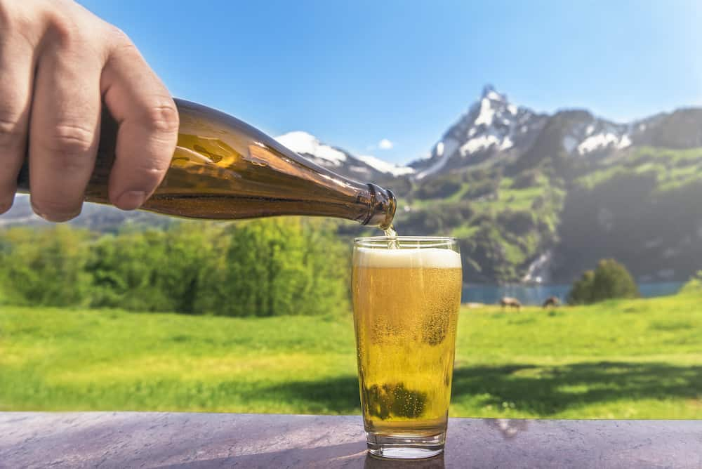 Glass of beer and summer alpine landscape - Hand of a man pouring beer from a bottle in a glass with a summer scenery in the background with mountains and green meadows, on a sunny day.
