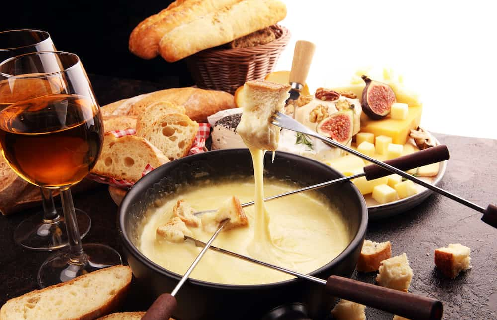 Gourmet Swiss fondue dinner on a winter evening with assorted cheeses on a board alongside a heated pot of cheese fondue with two forks dipping bread