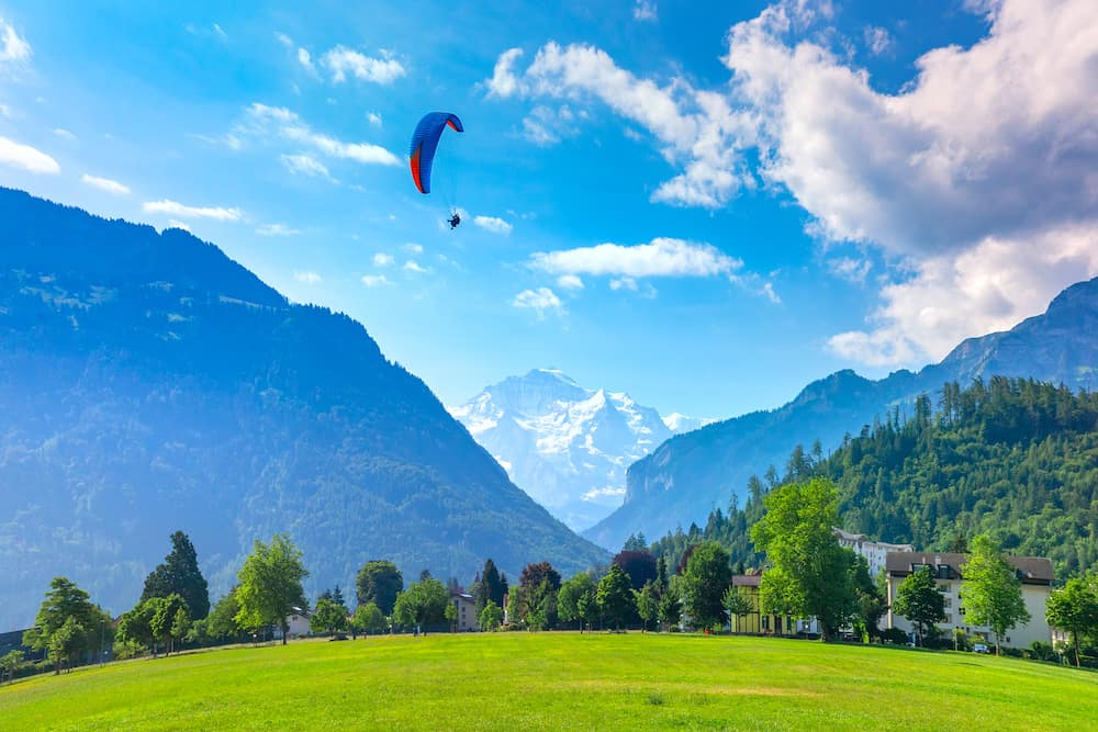 A paraglider flying at Hohematte Park in the center of Interlaken, important tourist center in the Bernese Highlands, Switzerland. The Jungfrau is visible in the background