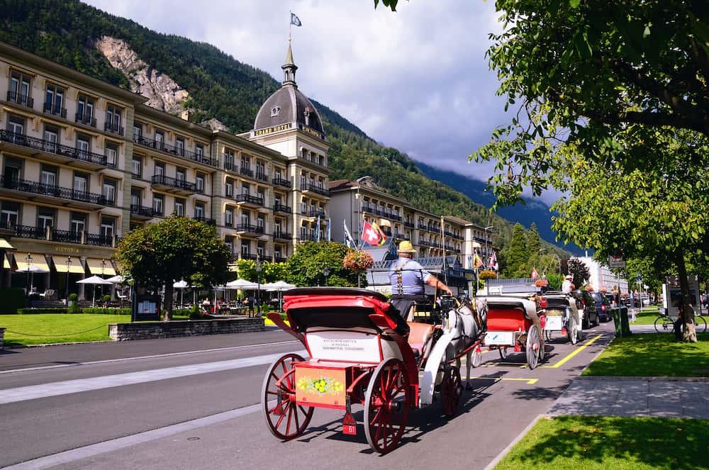 INTERLAKEN, SWITZERLAND - Main Street with Grand Hotel Victoria and Entertainment Horse Carriages in the Tourist Town of Interlaken in Canton of Bern on August 30, 2014 in Interlaken, Switzerland
