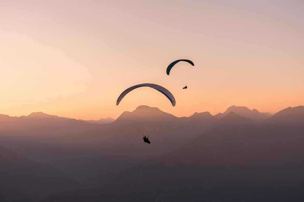 Paragliding over the Swiss Alps. Silhouettes of paragliders in the pink light of sunset.