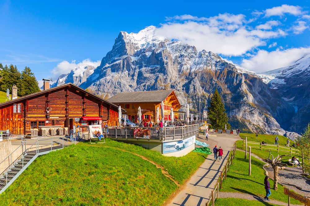 Grindelwald, Switzerland People at the middle station at First peak of Swiss Alps mountain, snow peaks panorama, Bernese Oberland, Europe