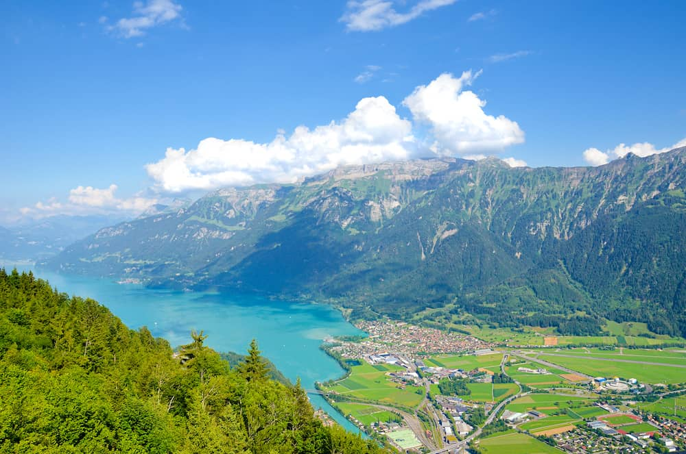 Turquoise Lake Brienz in Interlaken, Switzerland from above from Harder Kulm. Amazing Swiss landscape. Green hills, Swiss Alps. Summer Alpine landscapes. Nature