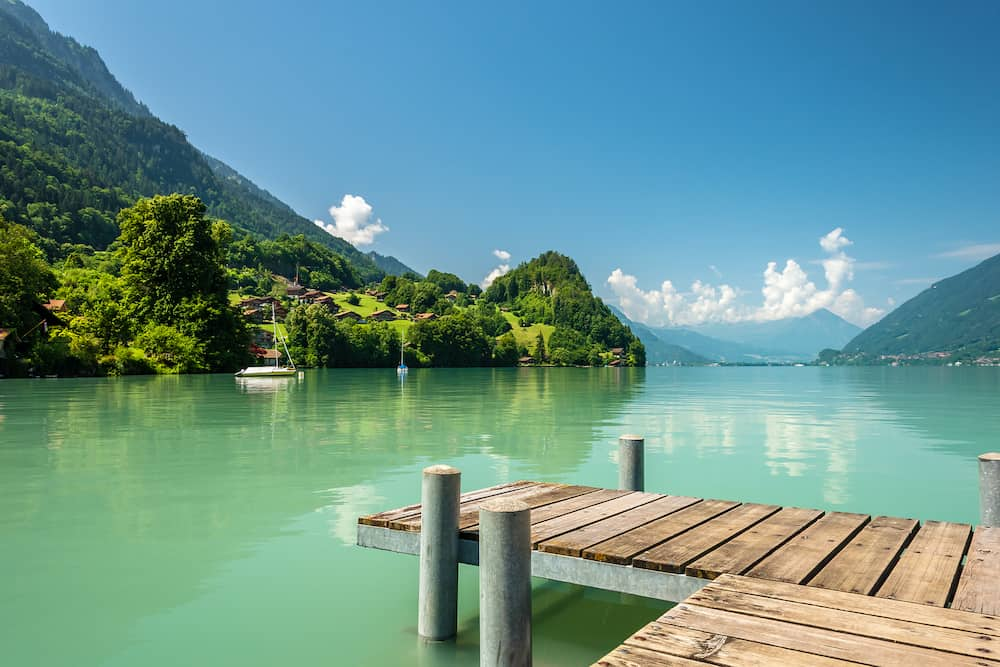 View of Brienz lake with clear turquoise water. Wooden pier. Traditional wooden houses on the shore of Brienz lake in the village of Iseltwald, Switzerland.