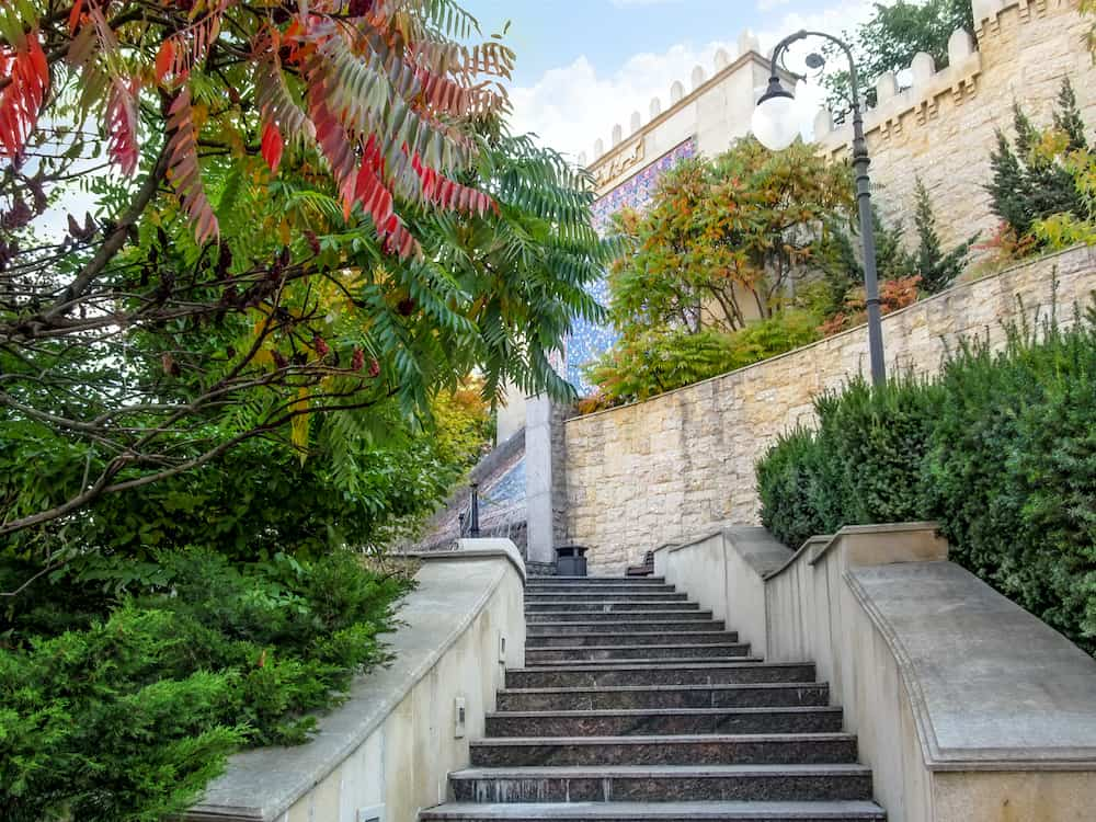 Kiev, Ukraine - Beautiful autumn landscape of Heydar Aliyev Park in Kiev. Amazing view of the alley with a staircase among the red, yellow and orange trees