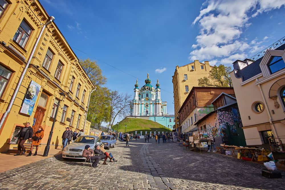 KIEV, UKRAINE - people and gift shops on Andriyivskyy Descent in Kiev city in spring. This street connecting Upper Town district and the historical commercial Podil district