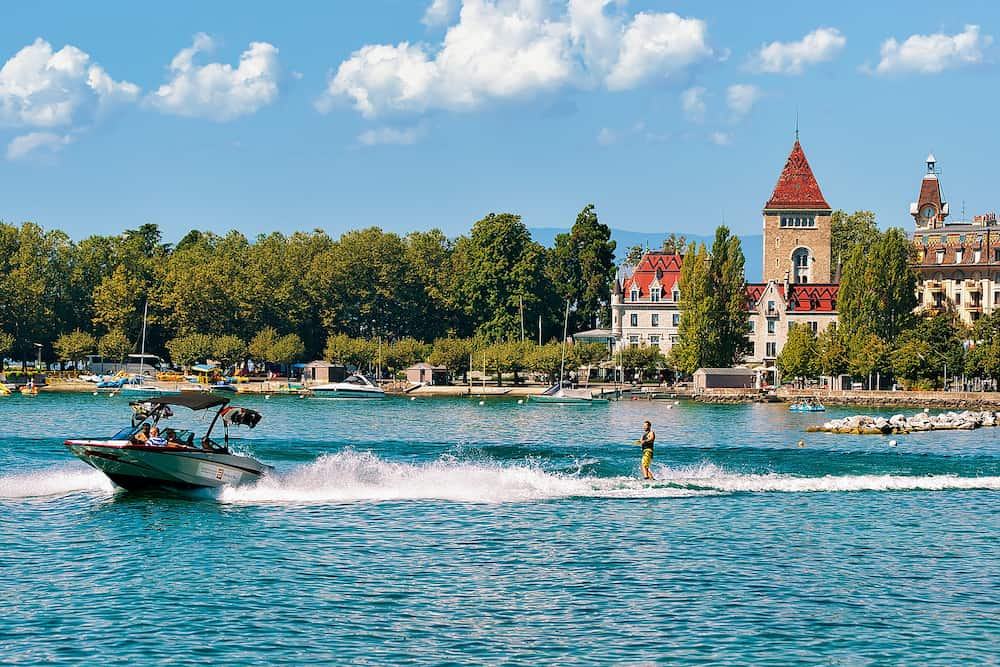 Lausanne Switzerland - Motorboat with man wakeboarding on Lake Geneva embankment near Chateau Ouchy in Lausanne Switzerland.