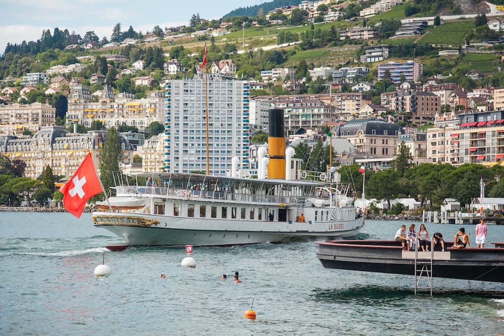 Montreux, Switzerland - The most beautiful steam boat called La Suisse with Swiss flag waving at the stern approaching Montreux pier on Swiss Riviera, Vaud, Switzerland on summer day