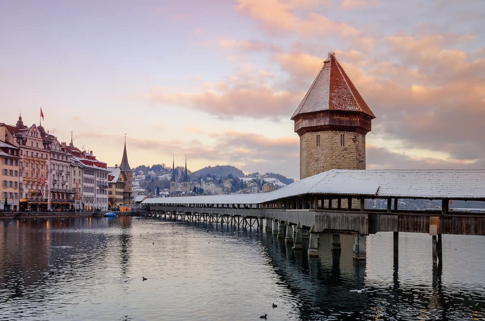 Historic city center of Lucerne with view of famous wooden bridge Kapelbrücke (Chapel Bridge) on river Reuss, stone tower Wasserturm. Europe, winter Switzerland.