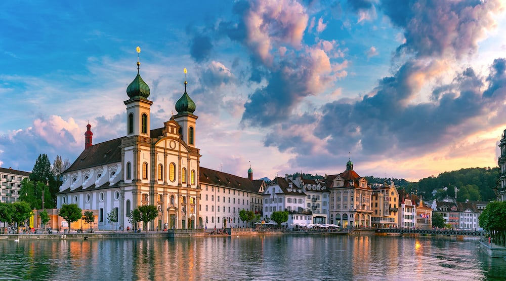 Jesuit Church and fairy tale houses along the river Reuss at sunset in Old Town of Lucerne, Switzerland