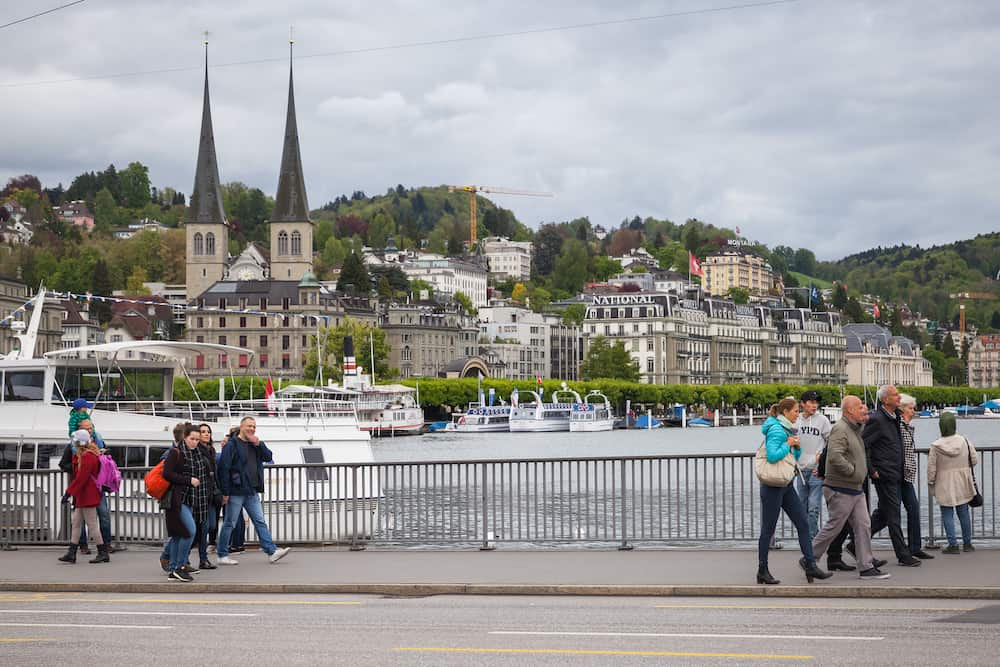 Lucerne, Switzerland - Ordinary people and tourists walk on the street of Lucerne city along Reuss river coast