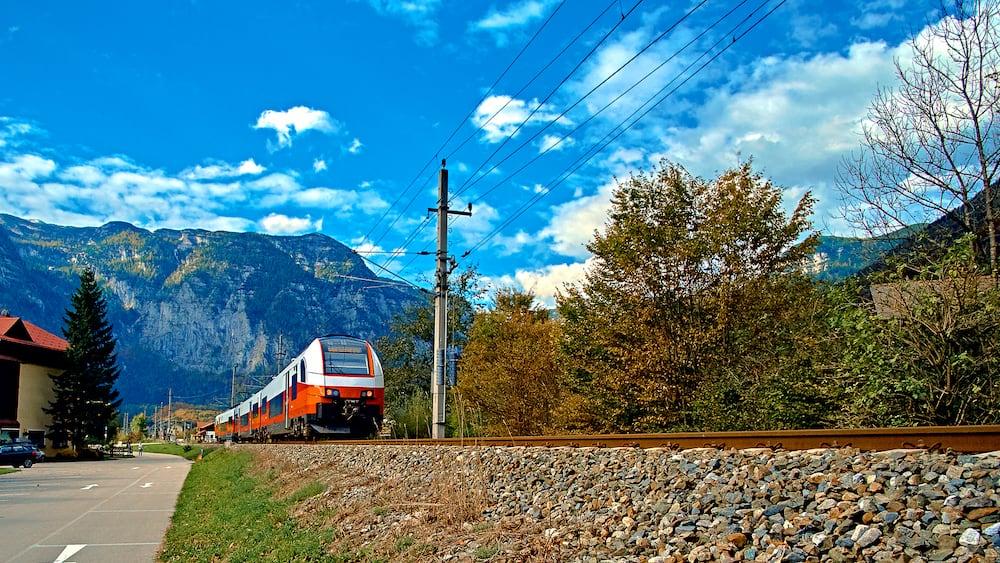 Red blue train in motion in Austrian alps mountains. High speed mountain train arrives at Hallstatt Obertraun train station in mountains. Location: resort village Hallstatt, Salzkammergut, Austria.