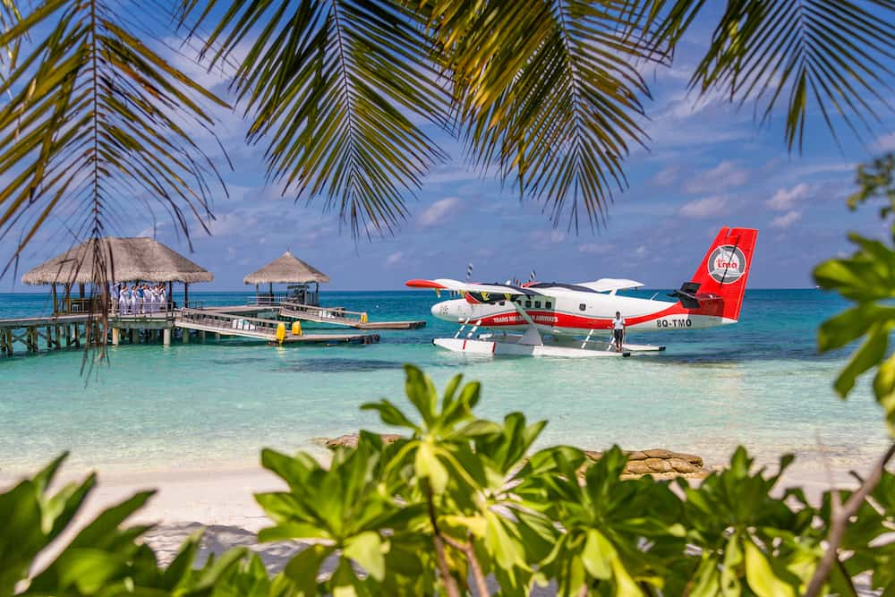 Ari Atoll, Maldives: Exotic scene with seaplane on Maldives sea landing. Vacation or holiday in Maldives concept background