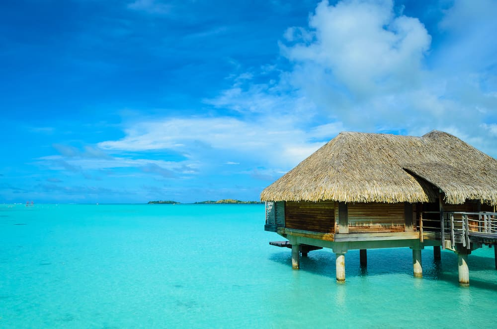 Luxury thatched roof honeymoon bungalow in a vacation resort in the clear blue lagoon of the tropical island