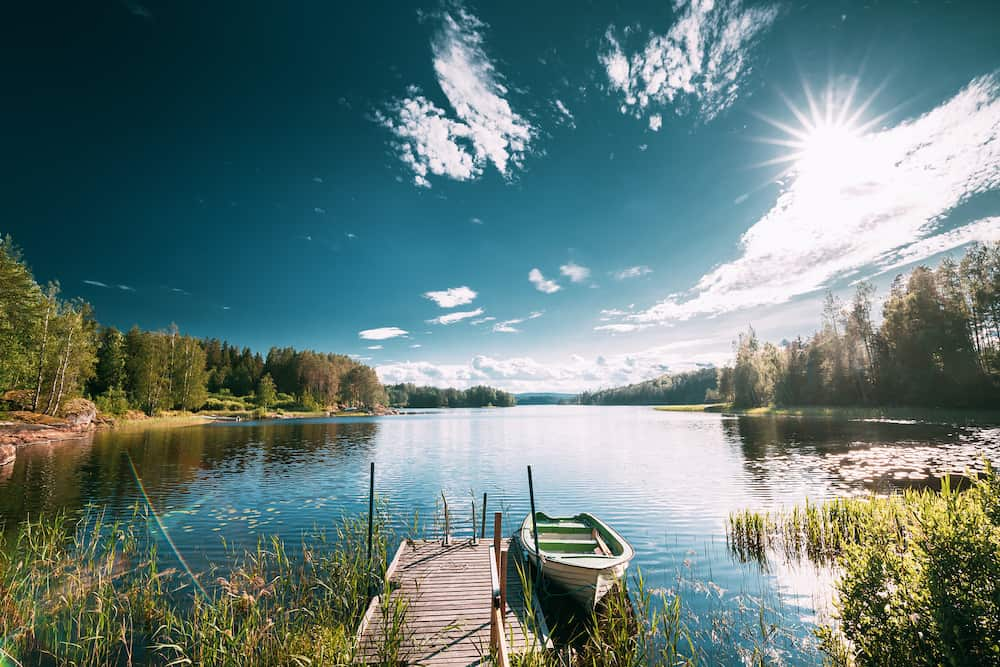 Old Wooden Fishing Boat Moored Near Pier In Summer Lake Or River. Beautiful Summer Sunny Day Or Evening. Swedish Nature. Arjang SV, Tocksfors, Sweden.