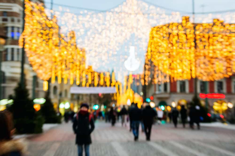 Defocused city of Malmo Sweden with Christmas decorations and pedestrian passing near Davidshallsbron - Funny shoe bridge