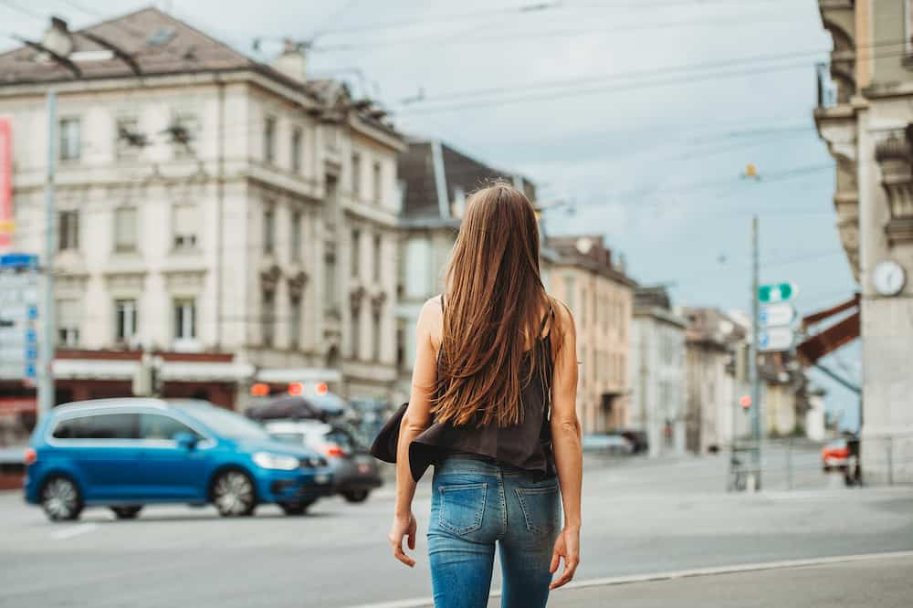 Outdoor portrait of beautiful young woman walking down the road in the city, wearing black cami top and denim jeans. Back view. Image taken in Lausanne downtown, place Bel Air, Switzerland