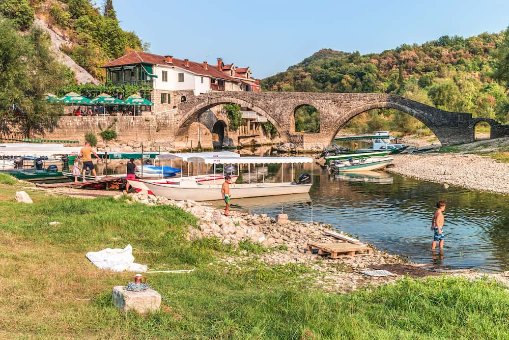 Podgorica, Montenegro - Old arched stone bridge across the river Crnojević. Boat pier and hotel at the source of the river.