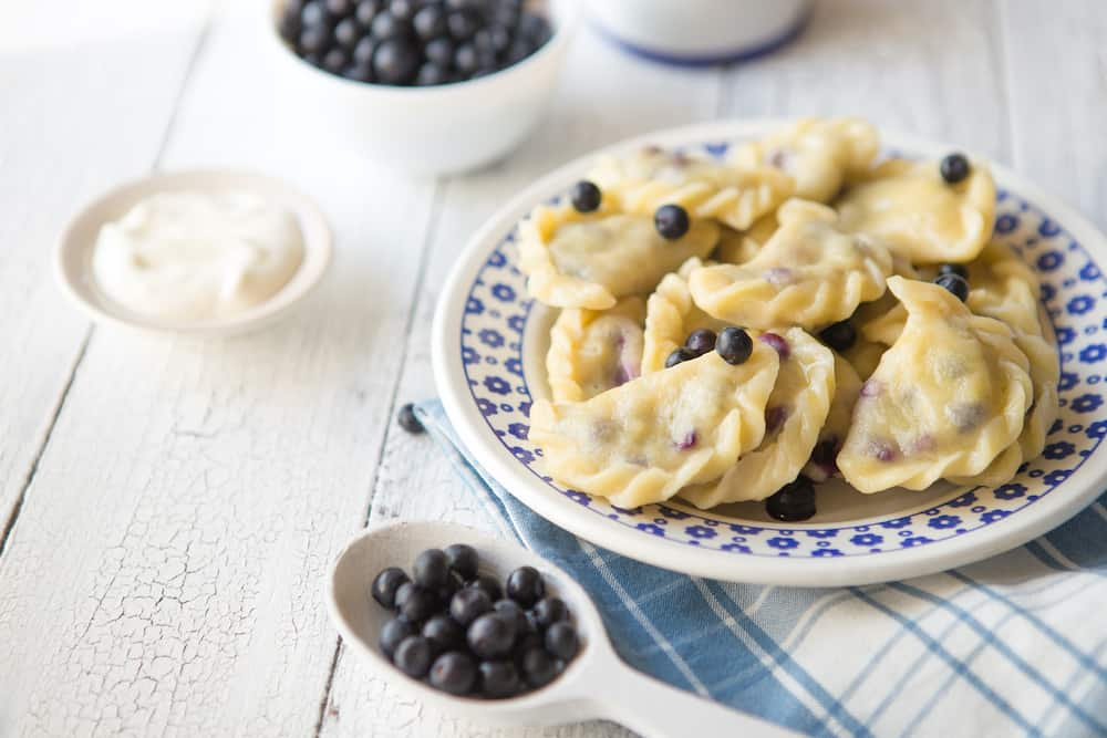 Preparing dumplings with blueberry. making pierogi or pyrohy, varenyky, vareniki. Traditional Russian cuisine, The traditional Ukrainian hand-made vareniki (dumpling) with blueberry inside