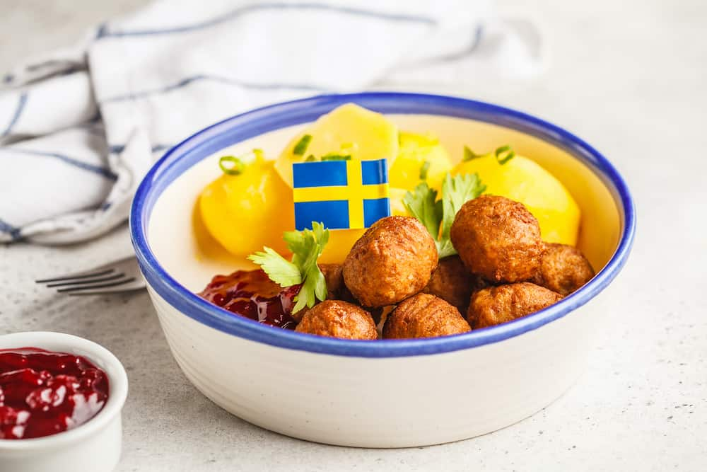 Swedish traditional meatballs with broccoli, boiled potatoes and cranberry sauce. Swedish food concept.