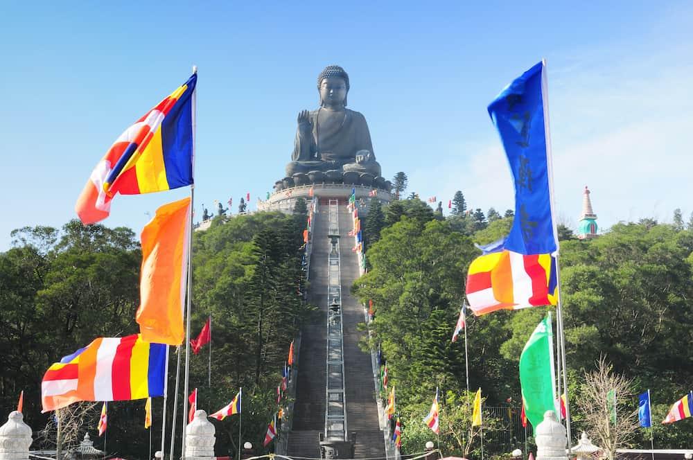 Tian Tan Buddha - The worlds's tallest bronze Buddha in Lantau Island, Hong Kong, China with colorfull flags